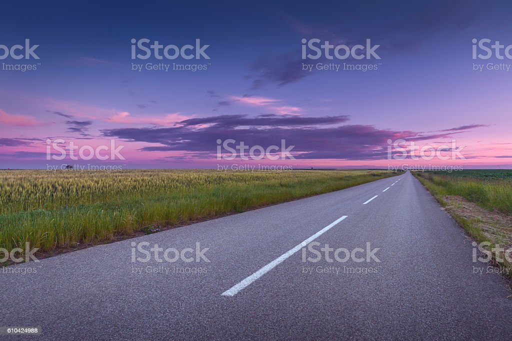 Driving on an open asphalt road at beautiful sunset stock photo