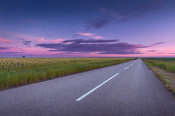 Driving on an open asphalt road at beautiful sunset - foto de stock