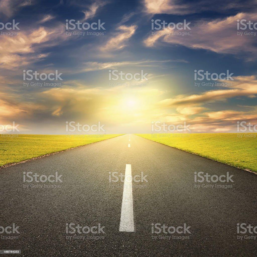 Driving on asphalt road towards the setting sun stock photo
