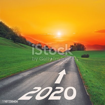 1170070487 istock photo Driving on idyllic open road against the setting sun forward on goals in the mountains to new year 2020. Concept for success, passing time and future. Empty asphalt road. 1167235404