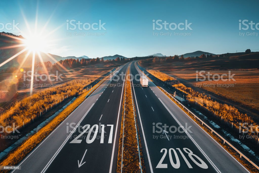 Driving on open road at beautiful sunny day from old 2017 to new year 2018. Aerial view stock photo
