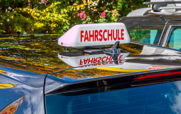 Driving school sign on the driving school car in German Driving school sign on the driving school car in German driving instructor stock pictures, royalty-free photos & images