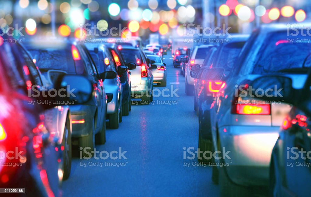 Driving slow in a traffic jam at night, rush hour stock photo