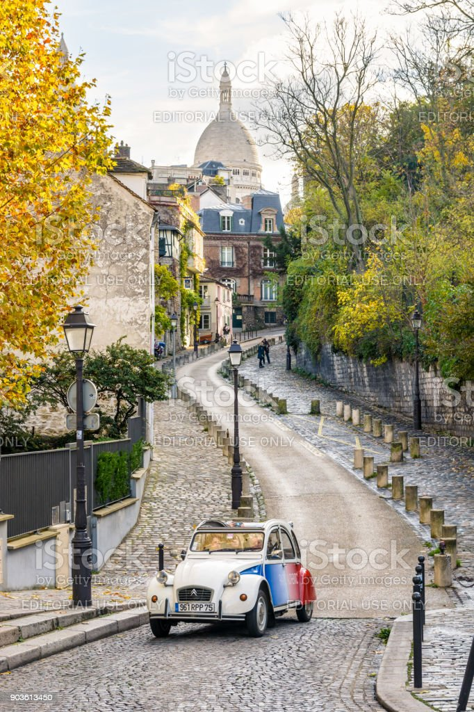 Driving the small streets of Montmartre on board a hired vintage french car with driver is a very popular way for tourists to explore the districts of Paris stock photo