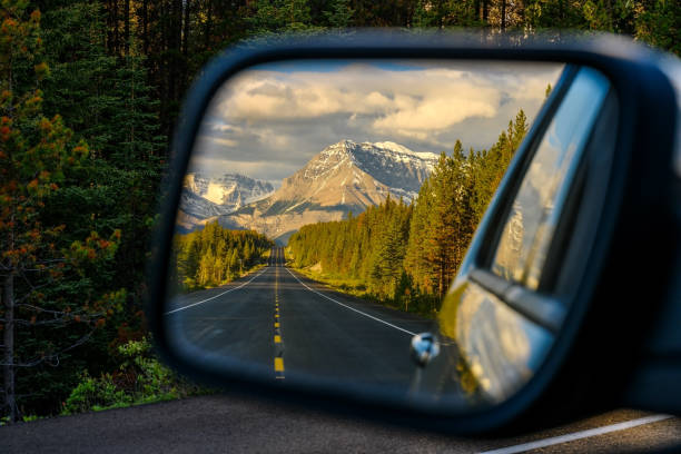 Driving through a mountain road and watching the beautiful scenery in the rearview mirror in the icefields parkway near Jasper Driving a car through a mountain road that leads through the Canadian Rockies and watching the beautiful scenery in the rearview mirror in the icefields parkway, Jasper National Park, Alberta, Canada road trip stock pictures, royalty-free photos & images