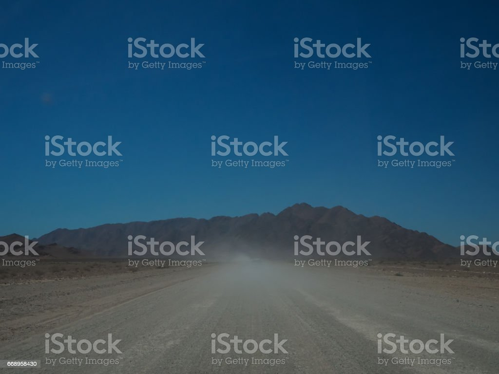 Driving through dusty unpaved road to rocky mountain  among desert landscape foto stock royalty-free