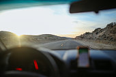 Man is enjoying a road trip through the desert in California during sunset hours.