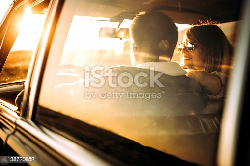 Young loving couple driving in car on sunny day,  rear view, photo is taken in car from 1980 year