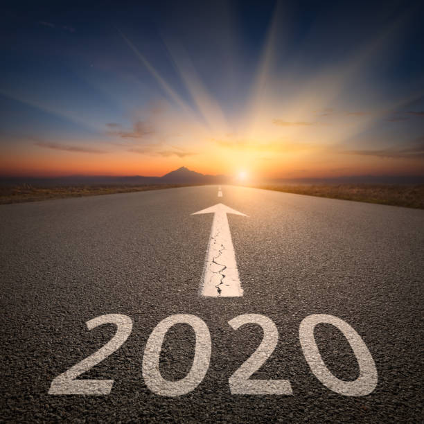 Driving to upcoming 2020 on open road at sunrise Upcoming 2020 new year on empty highway leading to the mountains through the desert against the rising sun. horizon over land stock pictures, royalty-free photos & images