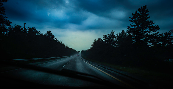 Dark stormy clouds and heavy rains on the highway during the summer road trip to work.