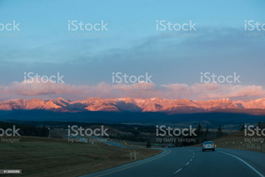 Driving towards the Canadian Rocky Mountains at Sunrise in Alberta, Canada stock photo