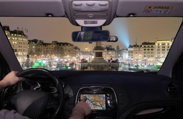 Driving using GPS towards  Trafalgar Square at night, London, UK - foto stock