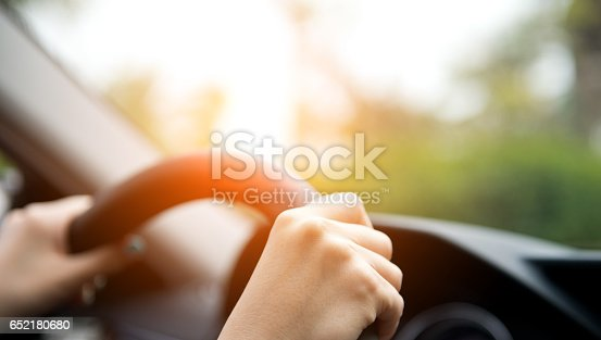 A woman in a luxury car, with her hand on the wheel.