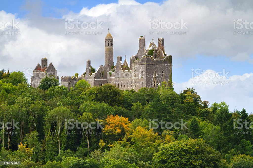 Dromore Castle atop a wooded hillside on a cloudy day stock photo