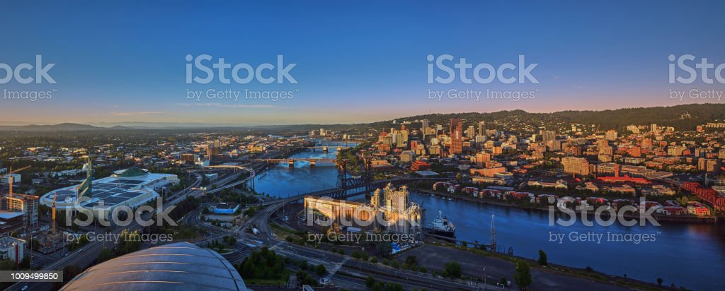 Drone aerial at sunrise with 6 bridges shot from over the top of the Moda Center of downtown Portland on a summer morning stock photo