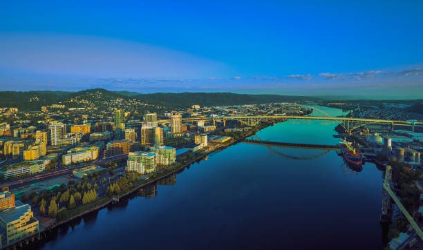 Drone aerial sunrise panorama of Portland waterfront with a ship loading cargo and the Fremont Bridge reflecting off the Willamette River stock photo