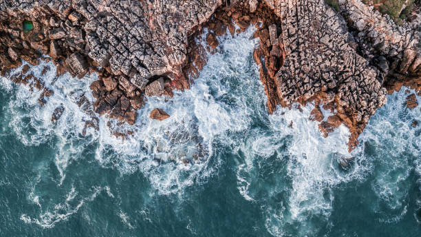 Drone aerial top view of sea waves hitting rocks on the beach with turquoise sea water. Amazing rock cliff seascape in the Portuguese coastline, Cascais. stock photo