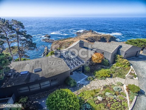 Drone aerial view of house by pacific ocean in Sonoma Mendocino California on sunny day by ocean