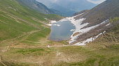 Drone aerial view of the Lake Branchino an Alpine natural lake during spring season. Italian Alps. Italy