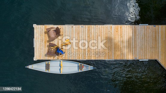 istock Drone aerial view of two Adirondack chairs on a wooden pier 1256422134