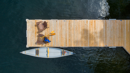 Drone aerial view of two Adirondack chairs on a wooden pier facing the blue water of a lake in Ontario. A yellow canoe is tied to the dock. Life jacket and oars are visible near the chairs.