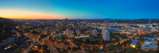 Drone aerial wide panorama on a summer evening at twilight of downtown Portland with the Freeway, Hawthorne, and Morrison bridges in view with Mt St Helens in the distance stock photo