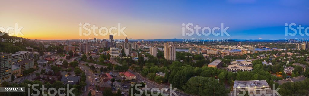 Drone aerial wide panorama on a summer evening at twilight of downtown Portland with the Ross Island, Tilikum, Freeway, Hawthorne, and Morrison bridges in view with Mt St Helens and Mt Hood in the distance stock photo