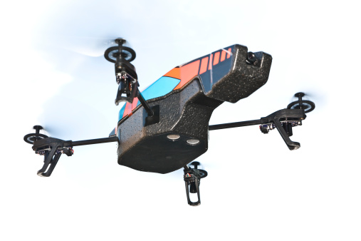 A quadricopter drone. The toy features two cameras (front and bottom). On white cloud sky.
