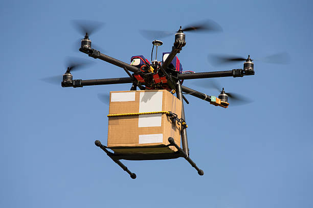 drone carrying parcel - drones stock photos and pictures