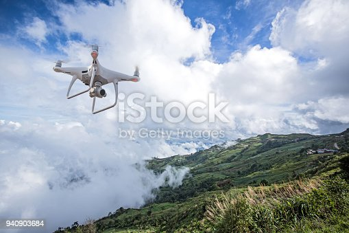 istock drone copter flying with digital camera.Drone with high resolution digital camera. Flying camera take a photo and video.The drone with professional camera takes pictures of the misty mountains. 940903684