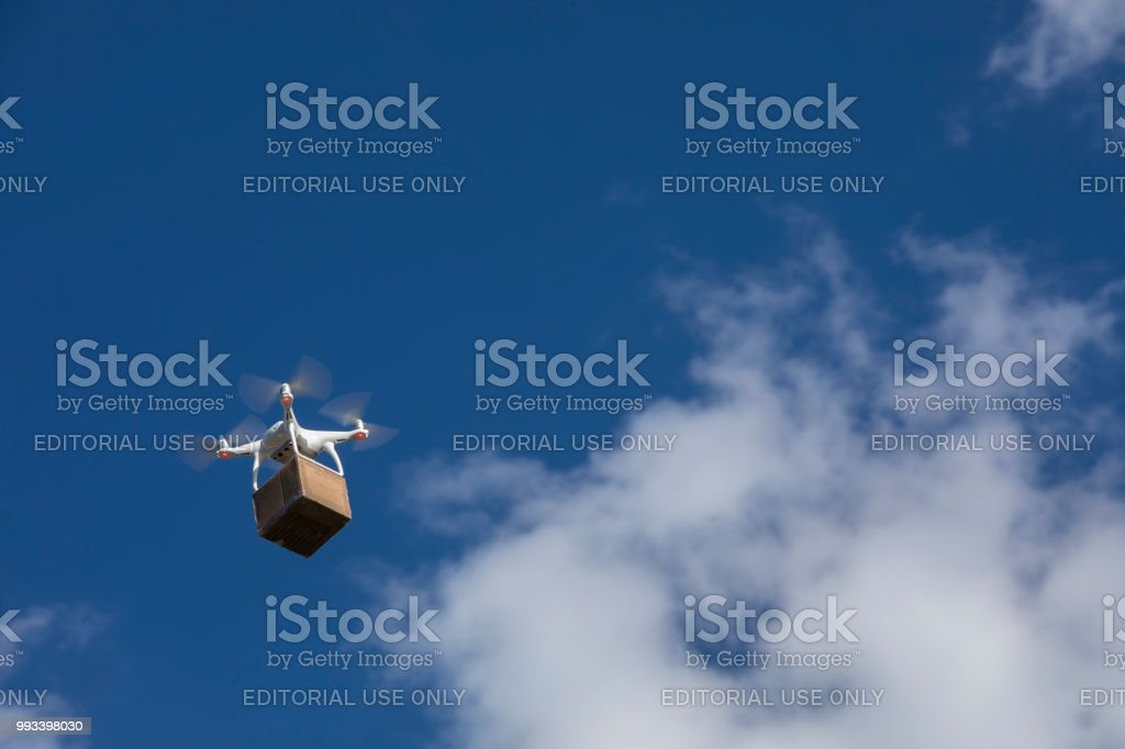 Drone delivering a cardboard box on a blue sky. stock photo