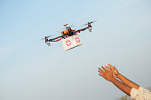 Drone Delivering First Aid Box or medicine to costumer hand during covid-19 or coronavirus lockdown - Advancing Medical Industry Logistics for Drug Transport concept