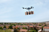 Delivery drone flying in city.\nIMPORTANT NOTICE:\nDrone made by me from households items exclusively for this image!