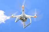 Drone DJI Phantom 4 in flight. Quadrocopter against the blue sky with white clouds. The flight of the copter in the sky.