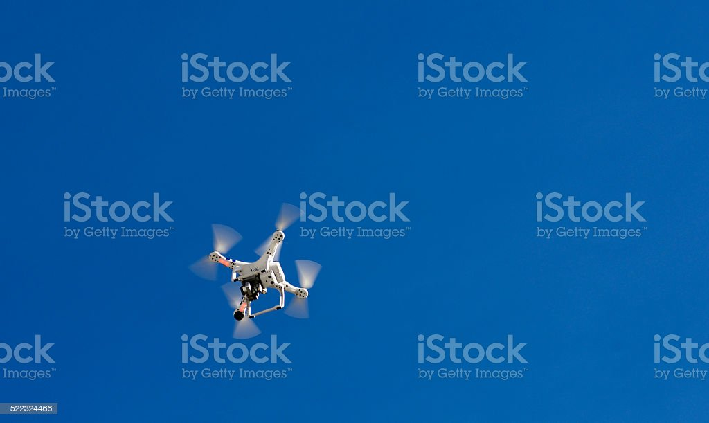 drone flying against a blue sky stock photo