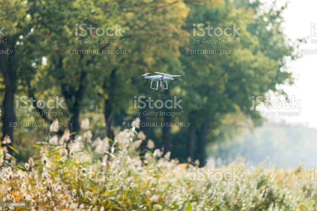 Drone flying beside an autumn forest area with gorgeous orange and...