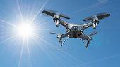 A drone flying in a blue sky under a shining sun
