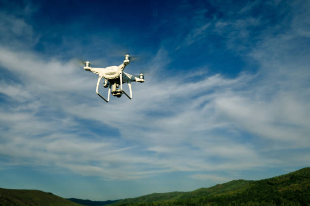 drone flying in the air over forest stock photo