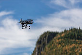 DSLR picture of a Drone flying over a Boreal Forest in Quebec on beautiful fall day. The drone is a Yuneec Typhoon Q500+ equipped with a 4k camera.