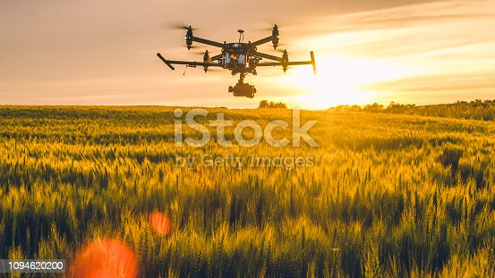 Drone flying over field at sunset