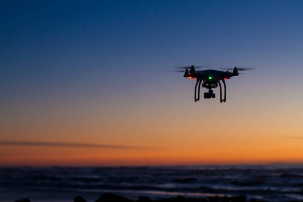 drone flying over ocean at dawn - drones stock photos and pictures