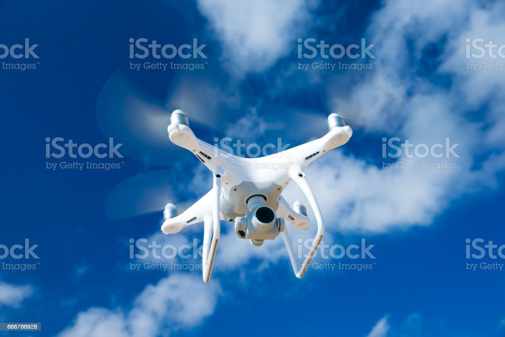 drone flying over sea. white drone hovering in a bright blue sky stock photo