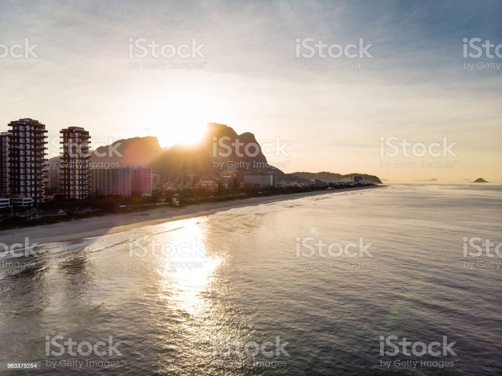 Drone flying towards Barra da Tijuca beach while filming waves crashing on beach during sunrise, with the buildings and the Gavea Stone mountain in sight - Zbiór zdjęć royalty-free (Bez ludzi)