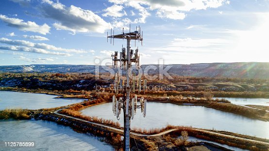 Beautiful shot of a modern cellular phone tower in a pretty setting with beautiful clouds