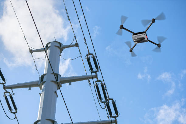 drone inspecting electricity power lines stock photo