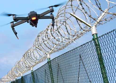 Drone monitoring barbed wire fence on state border or restricted area. Modern technology for security. Digital artwork with fictive vehicle.