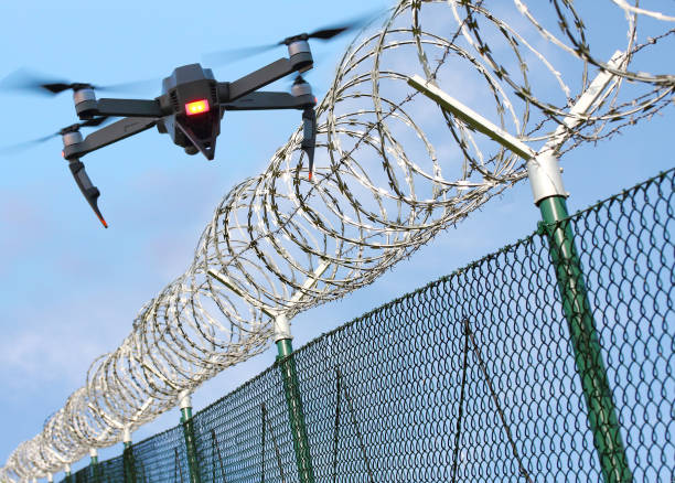 drone monitoring barbed wire fence on state border or restricted area. - drones stock photos and pictures