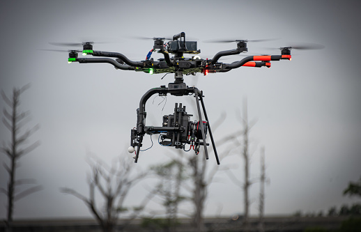 A digital cinema camera is affixed to a heavy duty drone.