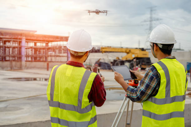 drone operated by construction worker. - drones stock photos and pictures