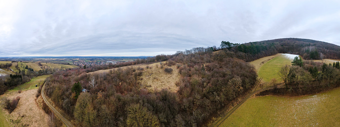aerial drone panorama of green hills with a little snow in Lower Austria at the edge of the Vienna Woods near Vienna